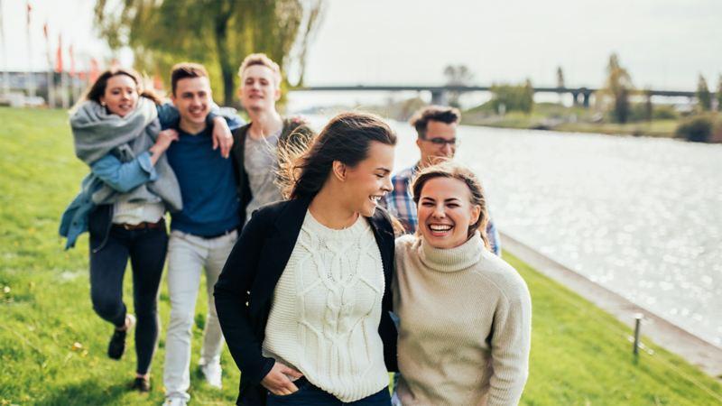 Eine Gruppe junger Menschen läuft am Wasser entlang