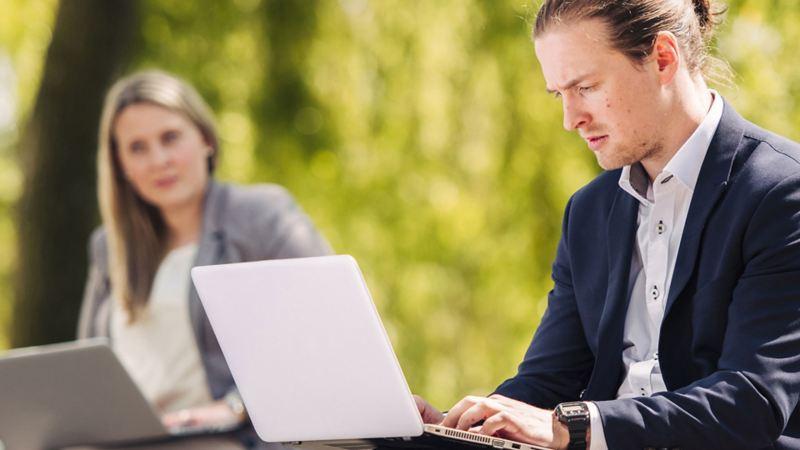 Eine Frau und ein Mann arbeiten im Freien an ihren Laptops