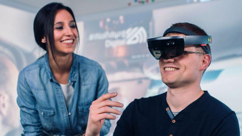 Eine Frau und ein Mann, der eine VR-Brille trägt, unterhalten sich in einem Lab bei VW