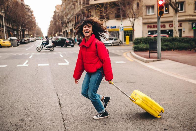 Eine Frau mit einem Koffer überquert die Straße