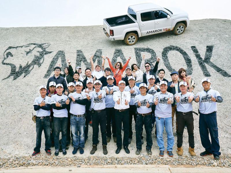 Amarok全地形試駕活動的工作人員,在環狀陡坡上AMAROK字樣及狼嚎圖騰前合照,銀色Amarok斜停在後方陡坡上