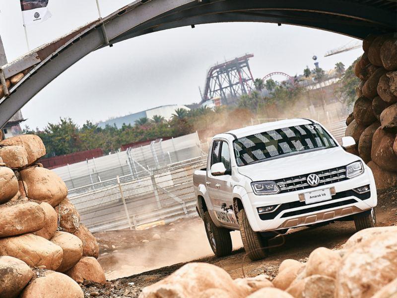 銀色Amarok V6行駛過大石圍繞的泥土地