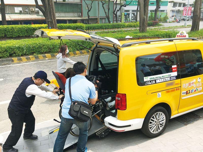 黃色Caddy IPC無障礙計程車,司機下車協助將坐在輪椅上的繞境民眾從後尾門推上車