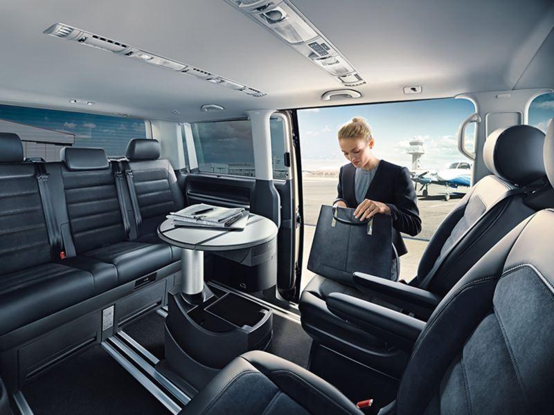 Multivan內裝照,車外金髮女子將公事包放在180度轉向後的第二排座椅翻找東西,中間圓桌沿滑軌移到與第三排的走道中間,即可成為行動會議空間