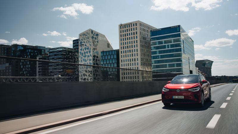 VW ID.4 GTX SUV sett fra siden, en kvinne og mann smiler på siden