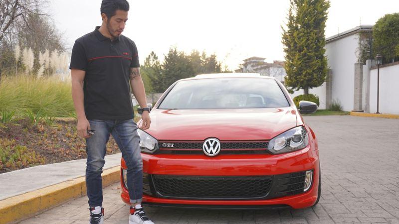 Alex frente a su Golf GTI rojo