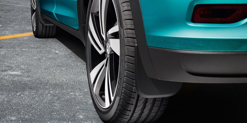 A turquoise VW T-Roc with polished rims and VW accessories mudflaps