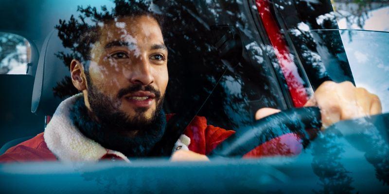 Uh homme conduit on véhicule et regarde au loin à travers son pare-brise propre