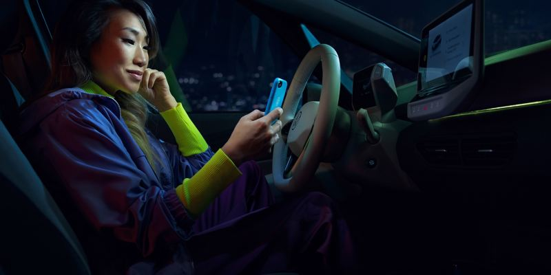 Una donna siede al posto di guida della sua Volkswagen ID.3 e connette il suo smartphone all'auto attraverso l'App WeConnect.