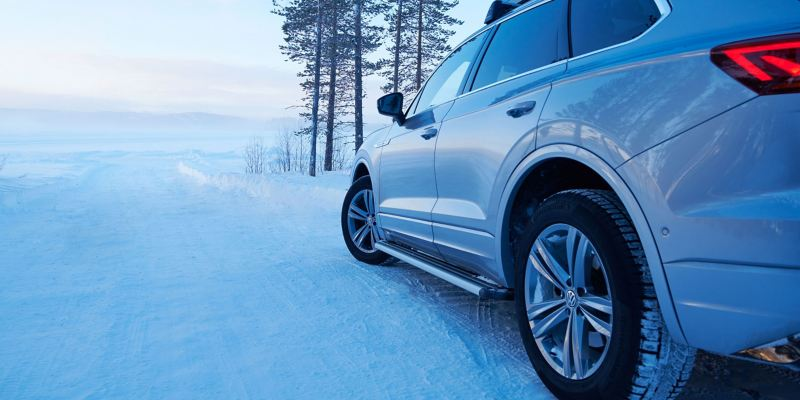 A silver VW car in a snowy landscape with winter tyres from Volkswagen Genuine Accessories