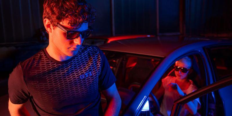 La touche et le feeling GTI – un homme et une femme portant des vêtements GTI et leur Volkswagen sportive