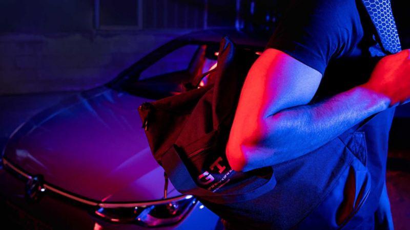 Un uomo con in spalla uno zainetto originale Volkswagen con la scritta GTI.