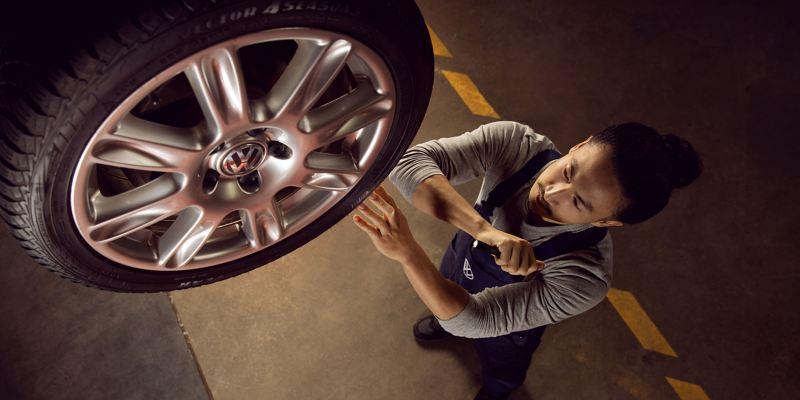 Un collaborateur du service entretien VW mesure la pression d'un pneu