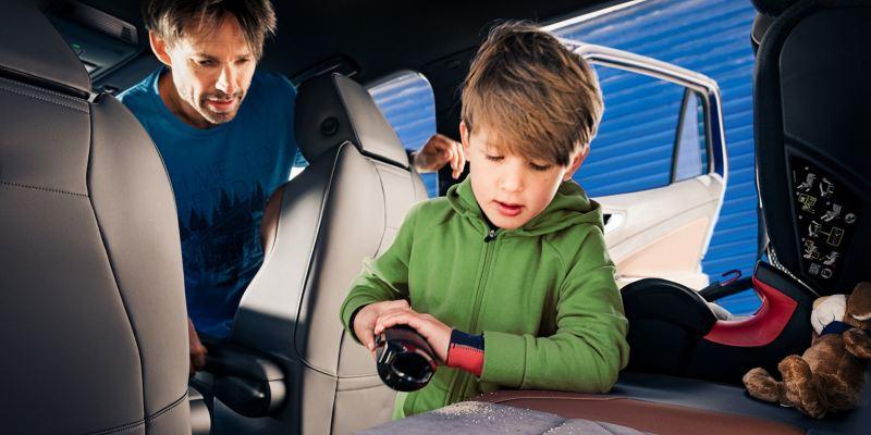 Un bambino gioca sui sedili posteriori di un'auto Volkswagen mentre il padre lo osserva dai posti anteriori.