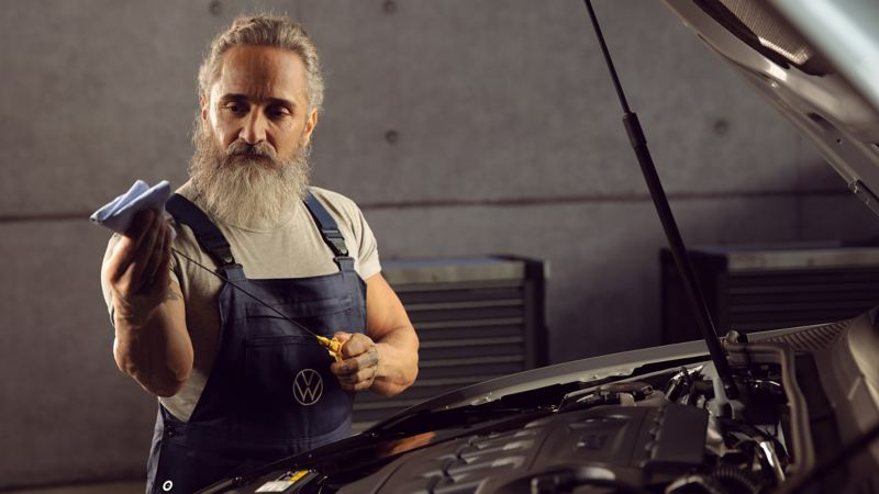 A VW service employee takes care of the engine oil and operating fluids of a Volkswagen