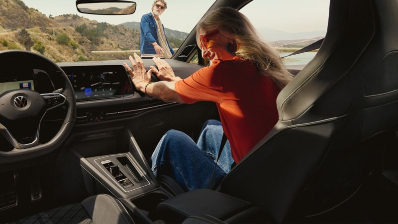 A woman enjoys her time inside her VW car with modern infotainment systems – Volkswagen interior