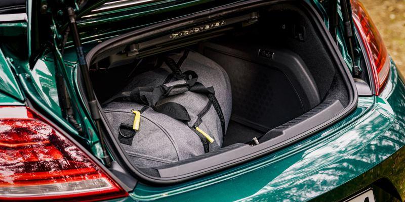 Dettaglio del vano portabagagli aperto di un'auto Volkswagen con dentro un borsone da viaggio.