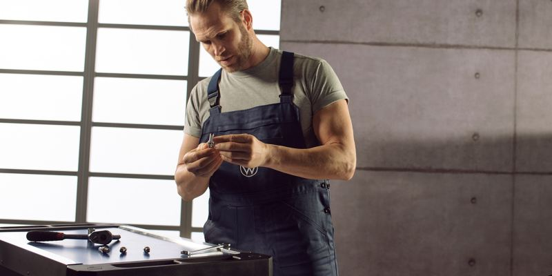 VW service employee holds a Volkswagen Genuine Spark Plugs in his hand