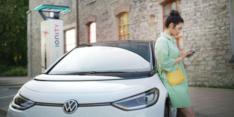 En kvinde tjekker opladningsprocessen for sin VW ID.-model med We Charge-appen.