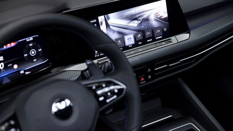 Plan rapproché du volant de la toute nouvelle Golf R 2022. Derrière celui-ci, on aperçoit le cockpit numérique à écran tactile affichant les divers modes de conduite.