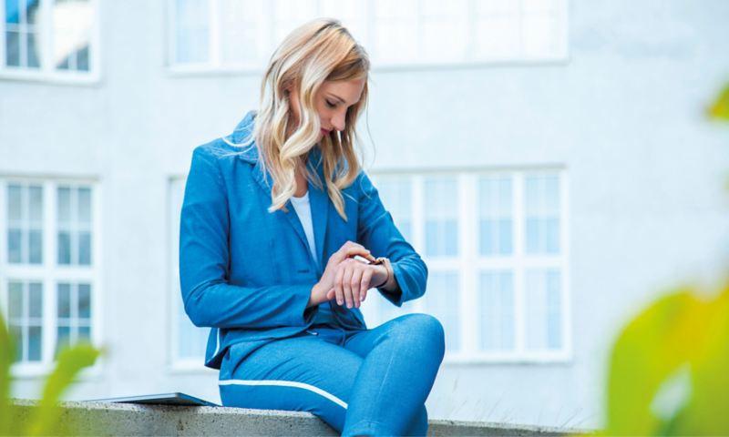 Caroline im blauen Hosenanzug schaut auf ihre Smart Watch