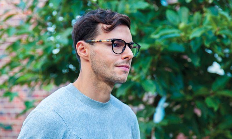 Julio mit Brille vor grünem Hintergrund