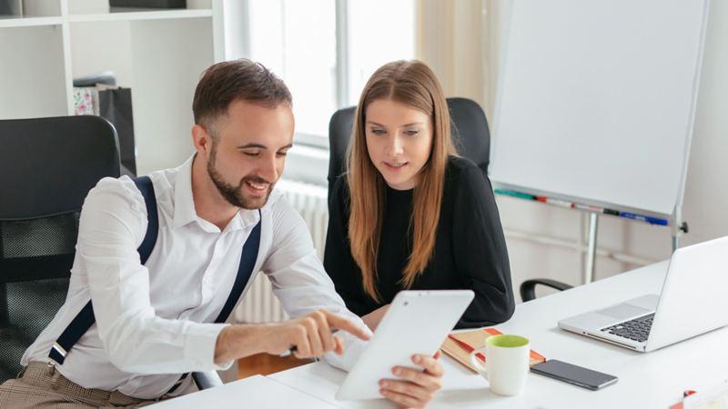 Eine Frau und ein Mann sitzen an einem Schreibtisch schauen gemeinsam auf ein Dokument