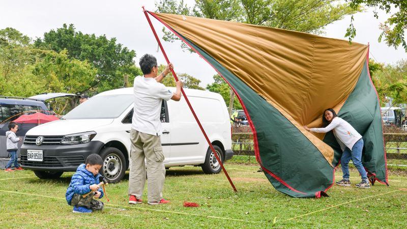 車主露營活動現場紀錄照,車主一家人在白色Caddy Van旁準備搭起帳棚
