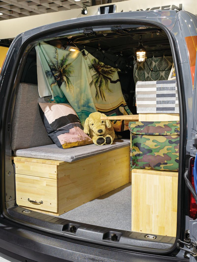 灰色Caddy Van改裝成VanLife露營車,尾門向兩側開啟可看到門上掛滿戶外運動小道具,後廂加上木箱堆疊成的座位、收納空間及工作平台