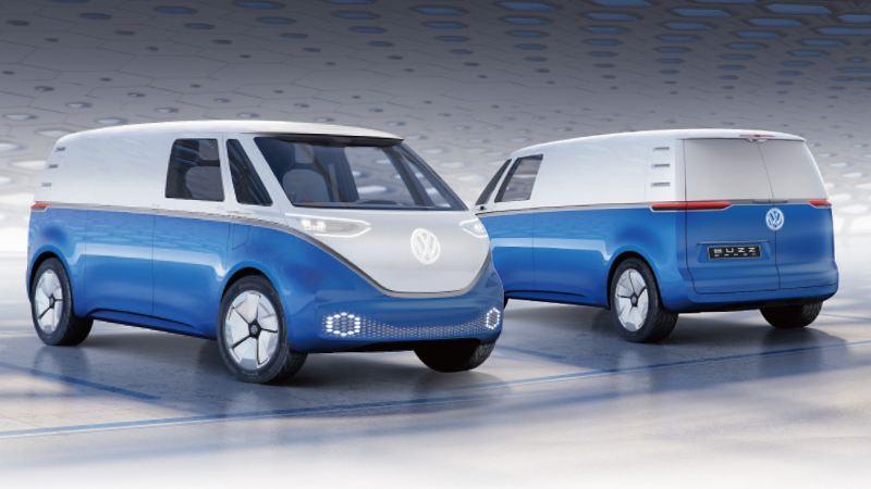 2台藍白雙色的電動概念車I.D. BUZZ 停在蜂巢式屋頂、充滿未來感的銀白色室內空間內,一台車頭往前、另一台車頭往後,因此可看見車尾也改成懸浮式把手,平整化外觀展現未來感