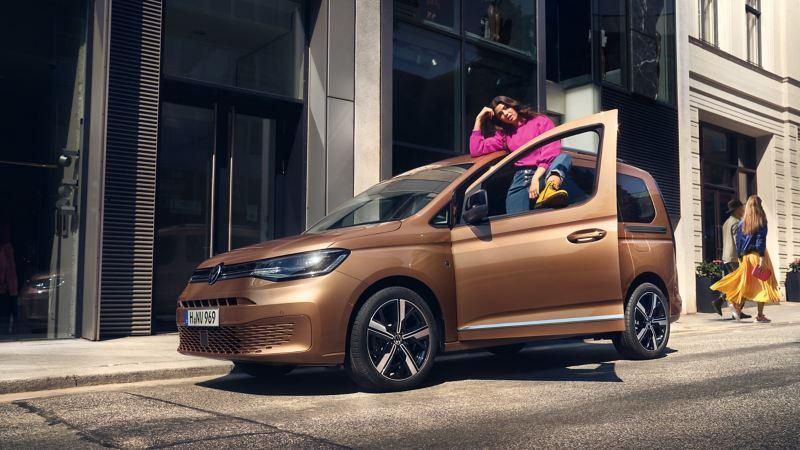 外觀情境圖-身穿桃紅色上衣女子打開金色Caddy Maxi駕駛座車門