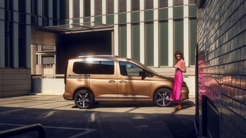 外觀情境圖-身穿桃紅色上衣女子站在金色Caddy Maxi前面,在一個現代感的街道