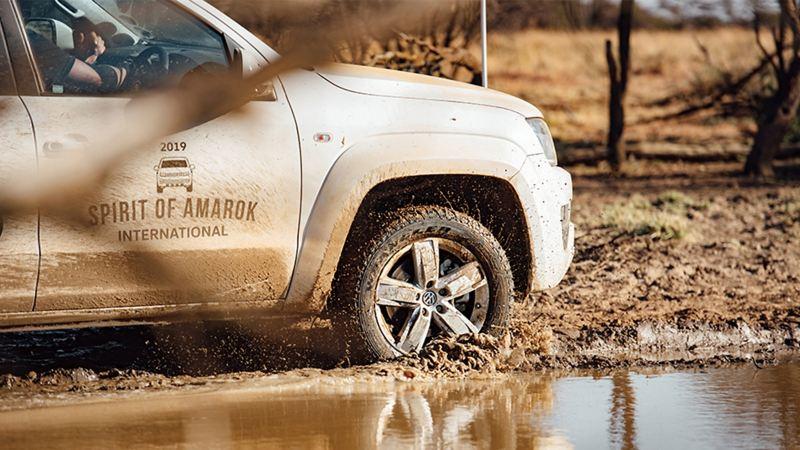 銀色Amarok 行駛過泥地上的水灘,水花濺起、車側也濺滿泥土痕跡