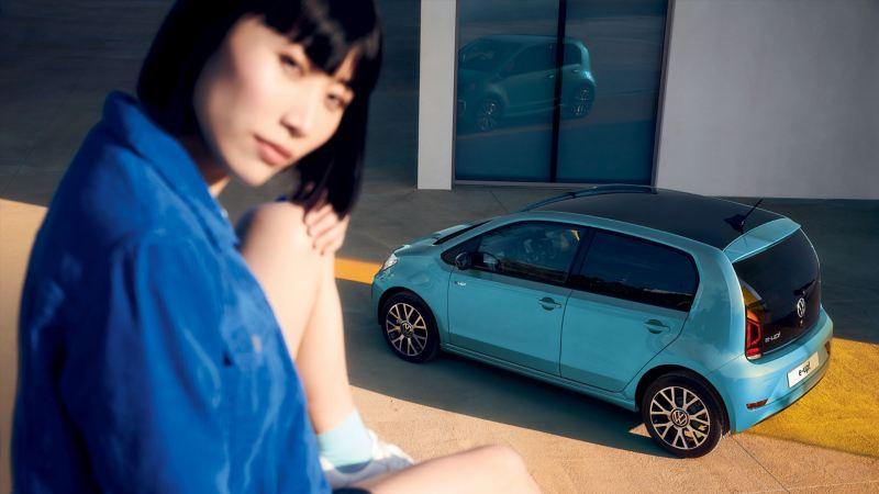 In primo piano una ragazza seduta su un muretto, sullo sfondo una Volkswagen Nuova e-up! vista dall'alto lateralmente.