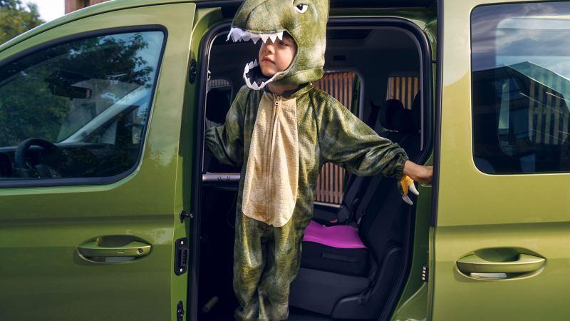 寬敞側滑門,綠色CaddyMaxi打開側滑門,有個小男孩穿恐龍裝佔在車門邊