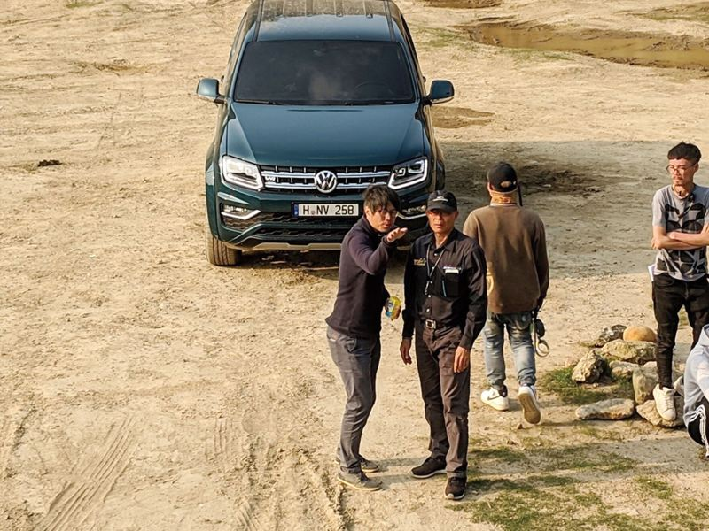 Amarok V6廣告拍攝現場紀錄,導演與攝影師站在黑色Amarok前討論拍攝內容