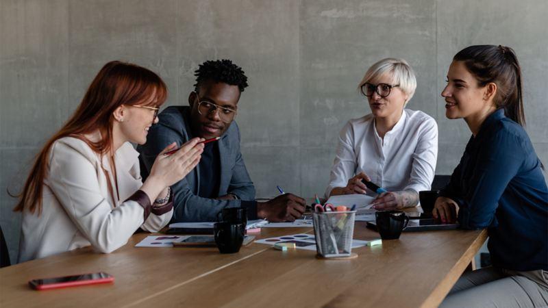 Vier Absolventen unterhalten sich an einem Tisch