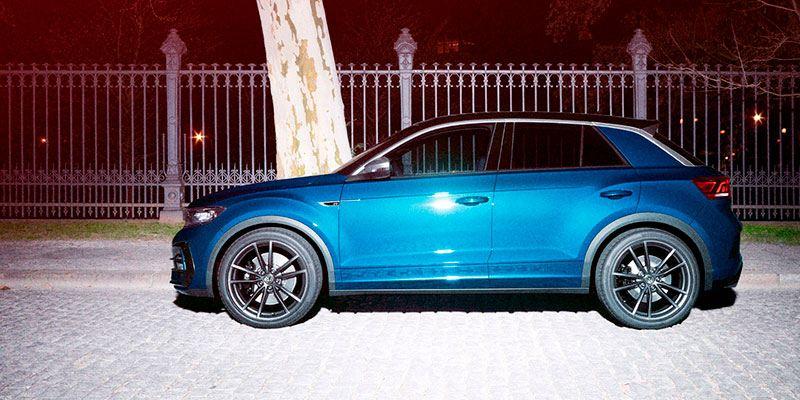 Vista lateral de un Volkswagen T-Roc R azul aparcado en la acera por la noche
