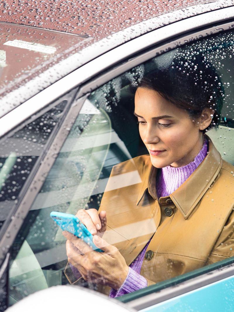 Una donna è seduta nella sua VW ID. e sta digitando qualcosa sul suo cellulare; aggiornamento VW over the air