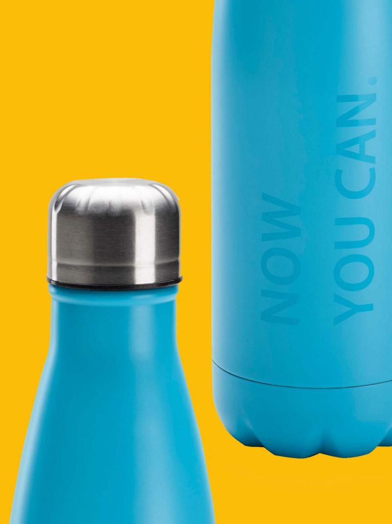 """Un bottiglia thermos originale Volkswagen di colore azzurro, con tappo di metallo e scritta """"Now you can""""."""