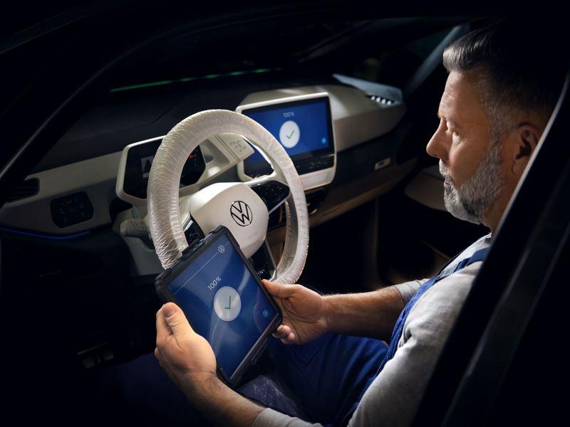 Un addetto Volkswagen Service siede a bordo di una ID.3 ed esegue l'aggiornamento del software tramite un tablet.