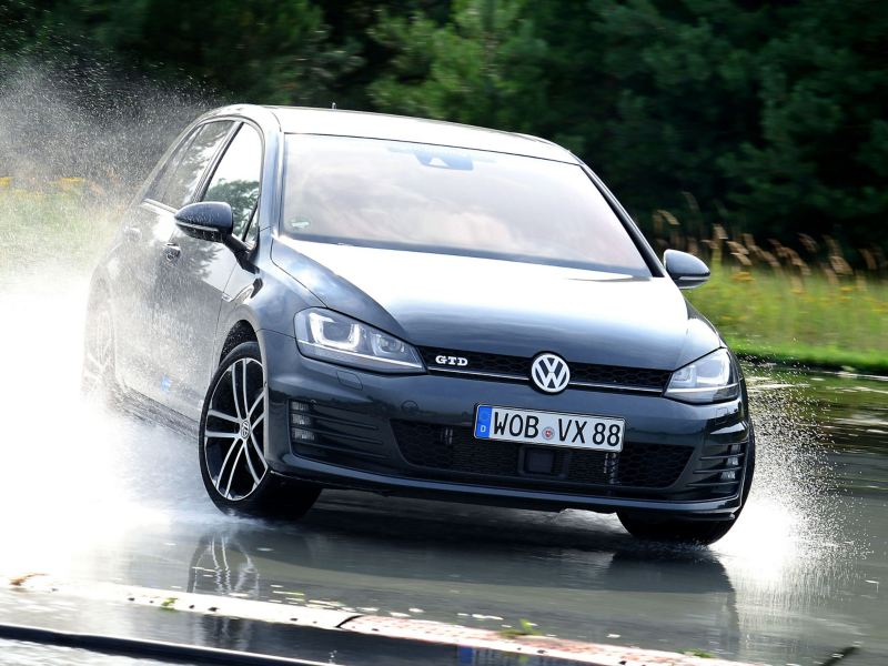 A blue VW Golf GTD with all-season tyres drives on a wet roadway and whirls up water