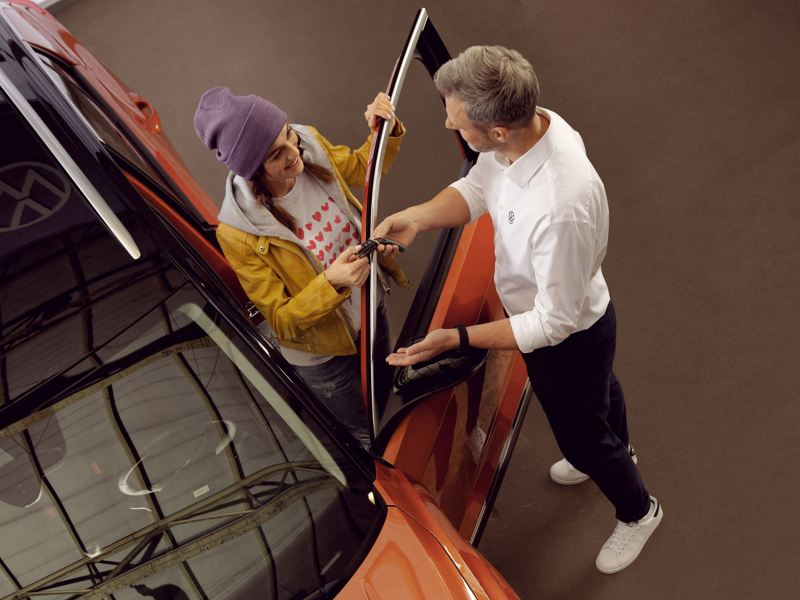 Un collaborateur du service entretien VW remet à une cliente la clé de sa Volkswagen – Service VW