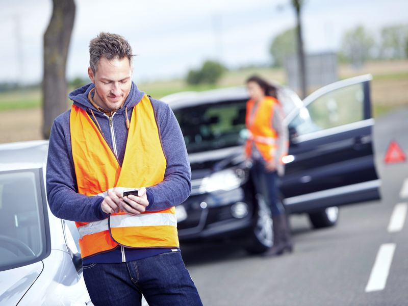 A man with a warning vest informs the VW breakdown and accident assistance via SMS about an accident