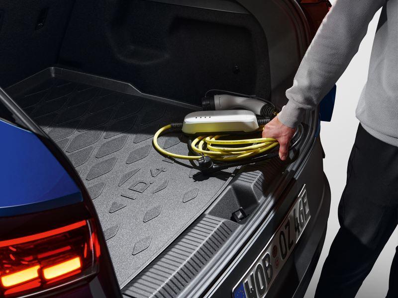 En Volkswagen fører tager sit Mode 2-ladekabel ud af bagagerummet på sin VW ID.4.