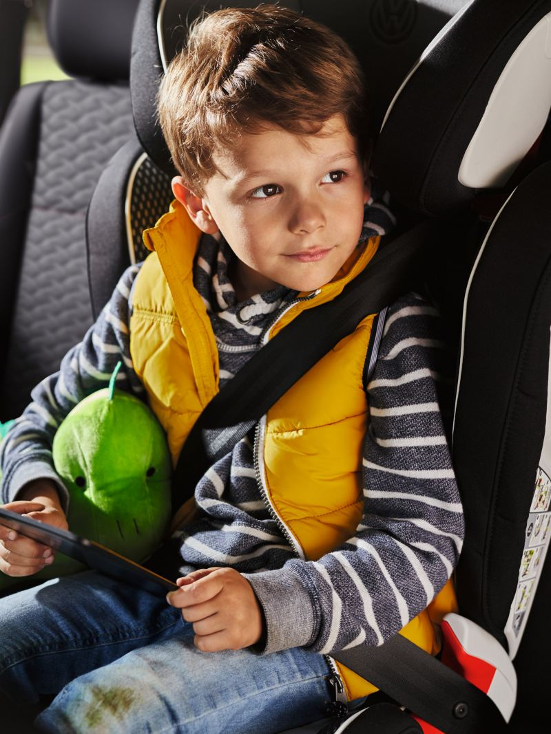 A happy boy with a plush dino watches a movie on a tablet, while sitting in a Volkswagen in a child seat
