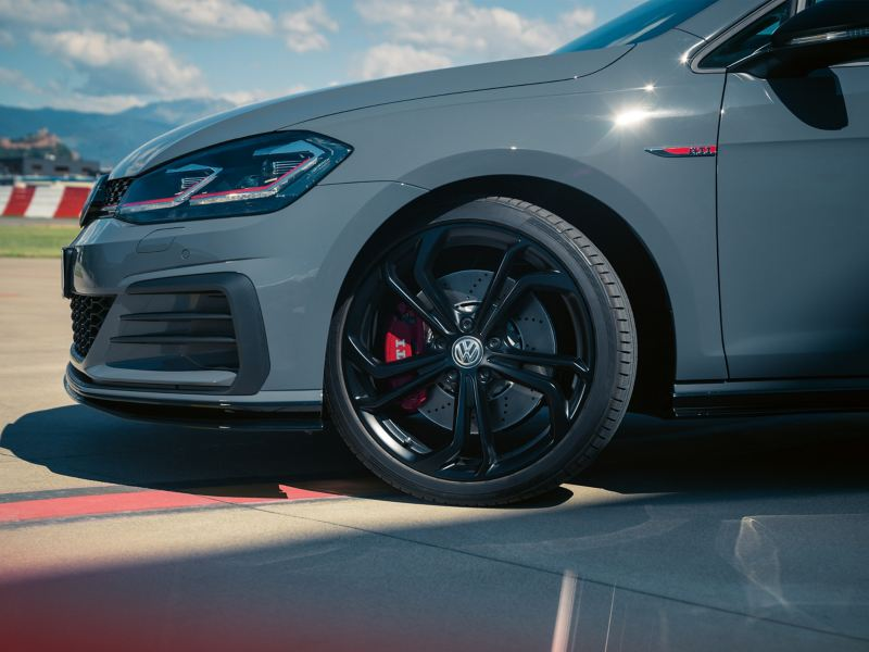 A grey Golf GTI TCR with complete wheels from a Volkswagen Partner on a racetrack
