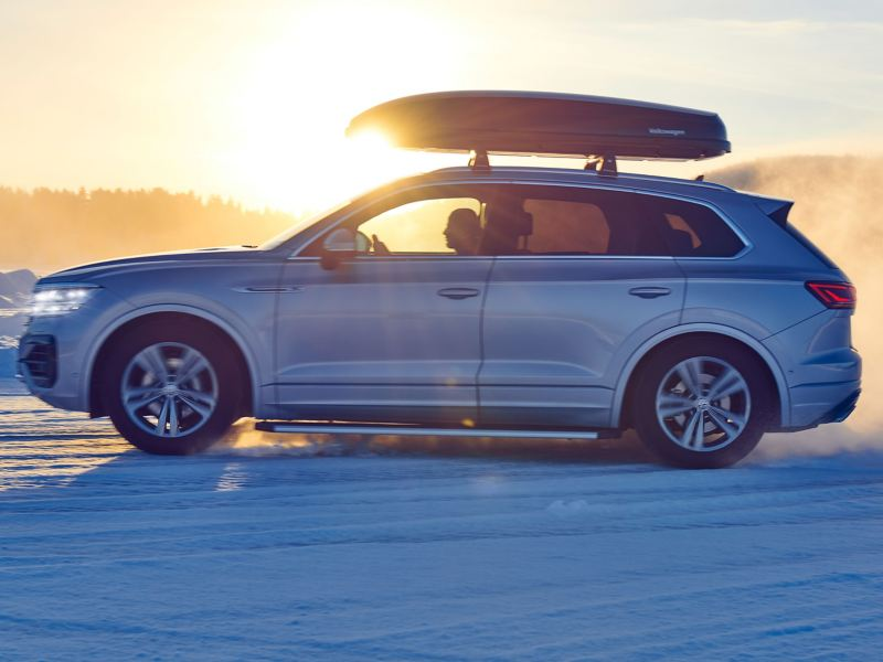 A silver VW car with winter tyres and a Volkswagen Accessories roof box in a snowy landscape