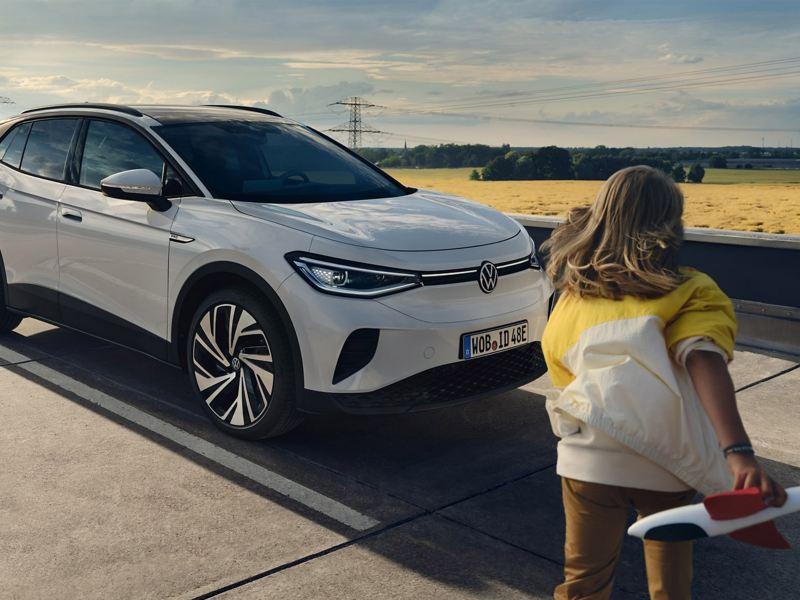 Un bambino si avvicina a una Volkswagen ID.4 in carica presso una colonnina.