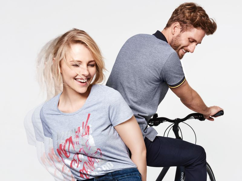 A woman and a man with clothes from the VW Lifestyle Collection sitting on a Volkswagen bike